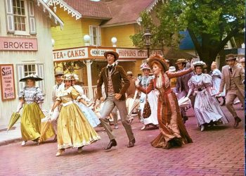 "Photo from Hello, Dolly! The Stars singing ""Put On Your Sunday Clothes,"" down faux stenciled cobblestone Front Street, on Garrison Landing. Copyright 1968, by 20th Century Fox. All rights reserved."